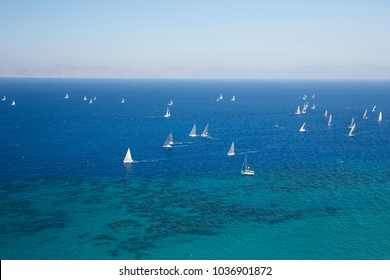 Ariel view to boats in the bay of Elli Beach, an island at the Rhodes coast, Greece. Sailboat or sailing boat is a boat propelled partly or entirely by sails smaller than a sailing ship.