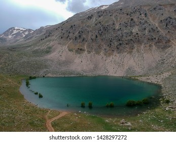 Ariel view of a green Lake, Turkey. A turquoise lake at the base of a mountain with stormy clouds. Trees are partially submerged in the lake