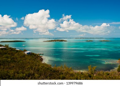 Ariel view of the ocean in the bahamas with crystal clear turquoise waters and bright blue sky with puffy white clouds