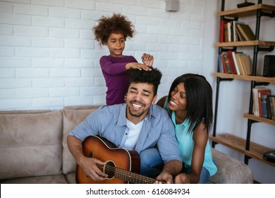 Arifcan american man playing some music on the guitar to his family.