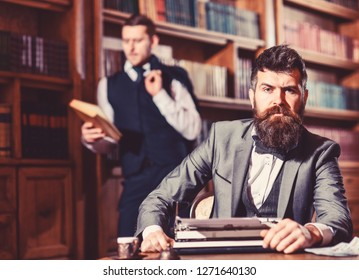 Aristocracy and elite concept. Man with beard and strict face near typewriter while his friend reading book on background, defocused. Men in suits, professors, aristocrats in library or retro interior