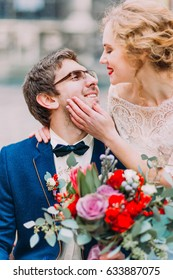 Aristocratic blonde bride softly touches her groom's face