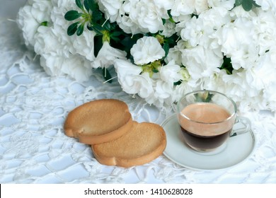 aristocratic equipment of the breakfast table, with white azalea flowers, cup of coffee and biscuits with jam