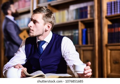 Aristocrats and elite concept. Young men with antique bookshelves on background. Educated elite or aristocrats spend leisure in library. Intelligent, man in suit with good manners hold cup of tea.