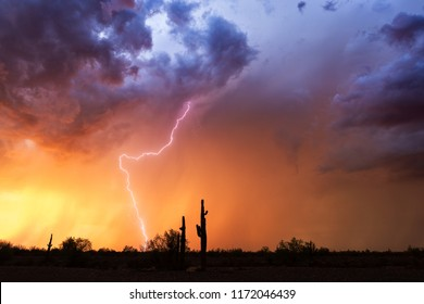 Arizona desert landscape at sunset with lightning, dramatic storm clouds, and colorful sky.