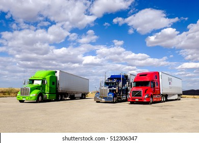 ARIZONA, USA - MARCH 15, 2015: A trio of 18-wheeler trucks are parked under the sun at a truck stop in the Arizona desert on the road from Nevada to Texas.
