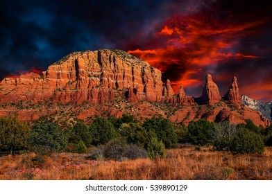 Arizona,Sedona, Cathedral rock mountain range sunset; beautiful deep red skies at sunset blanketing the desert and red oxide rock with rich warm hues.