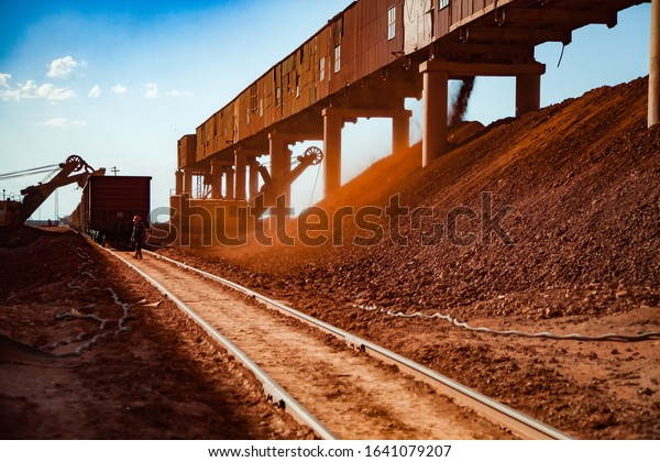Arkalyk/Kazakhstan - May 15 2012: Bauxite clay open-cut mining. Loading and railway transporting terminal. Excavator loading aluminium ore. Hopper car train and worker on rails.