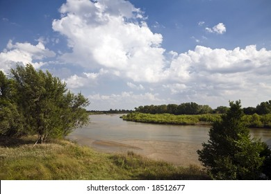 The Arkansas River meanders over the plains north of Wichita, Kansas under a partly cloudy sky