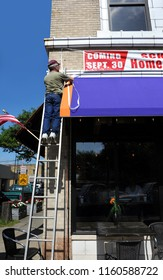 """Arkansas Sign Company Owner hangs a """"Grand Opening"""" sign on a business in downtown.  He is standing on a ladder wearing jeans and a red cap."""
