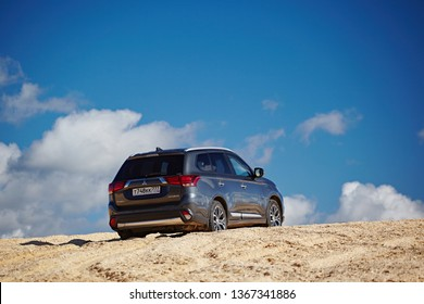 Arkhangelsk region, Russia - August 2017: Mitsubishi Outlander car rides through the sandy desert on the sand dune, against the blue sky with white clouds on a bright sunny day. Extreme Adventure