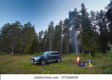 Arkhangelsk region, Russia - August 2017:  Mitsubishi Outlander car against the backdrop of the forest landscape in the evening. The bonfire, there is smoke, the tourists have come to rest