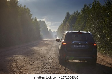 Arkhangelsk region, Russia - August 2017: Mitsubishi Outlander car rides on a dirt road in the forest. Saparion after rain forms fog in the sun