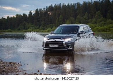 Arkhangelsk region, Russia - August 2017:  Mitsubishi Outlander car rides on the river, flying spray of water in the headlights of the car, against the backdrop of the summer landscape in the evening