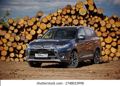 Arkhangelsk region, Russia - August 2017:  Mitsubishi Outlander car against the background of stacks of logs. Timber harvesting. Front view