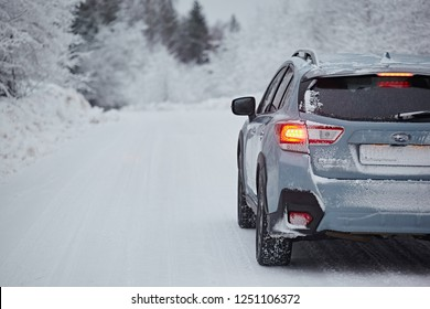 Arkhangelsk region, Russia - January 2018: A car Subaru XV is driving along a winter road amid a snowy forest after a snowfall in cloudy weather. Driving in the dangerous conditions of the north