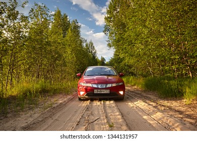 Arkhangelsk region, Russia - July 2018: Red car Honda Civic rides on a sandy road on the background of green trees in the sunset light. summer holidays