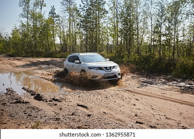 Arkhangelsk region, Russia - July 2018: white car Nissan x-trail rides on a muddy puddle, splashes fly against the background of the summer landscape and tree