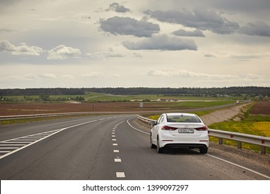 Arkhangelsk region, Russia - May 2018: White car Hyundai Elantra on the background of the asphalt road and the northern forest. The track goes away. Rear view