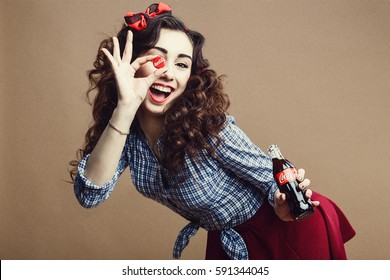 Arkhangelsk, Russia - january 10, 2017: Happy Beautiful Pin Up Girl Holding Cup of Glass Bottle as OK Symbol and Giving you a Soda. Woman Dressed in Red Skirt and Blue Plaid Shirt.