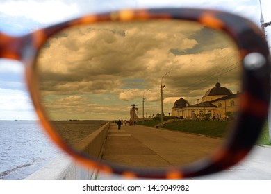 Arkhangelsk, Russia - June 02, 2019: view through polarized glasses on Northern Dvina quay, Gostiny dvor (Old Merchant Court, mediaeval trading establishment) and people walking on a windy cloudy day