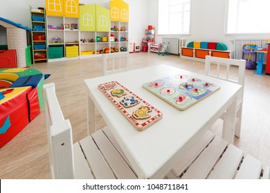 Arkhangelsk, Russia - march 3, 2018: Desk for lessons with toys in bright white game room in the kindergarten. Close up.