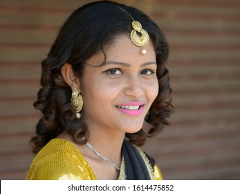ARKHET BAZAR, NEPAL - MAY 14, 2019: Young, dressed-up Nepali Chhetri woman with traditional forehead jewelry and large earrings smiles for the camera, on May 14, 2019.