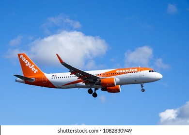 Arlanda, Stockholm, Sweden - April 27, 2018: Easyjet, Airbus A320-214 flying by in white clouds and blue sky, landing at Stockholm Arlanda Airport / ARN. Jet aircraft / plane.