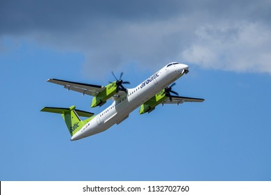 Arlanda, Stockholm, Sweden - July 10, 2018: Air Baltic, Bombardier Dash 8 Q400 take off in white clouds and blue sky at Stockholm Arlanda Airport / ARN. Propeller aircraft / plane.