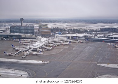 ARLANDA, SWEDEN - DECEMBER 31, 2018: Parked airplanes at gates aerial view, snow and ice on airport tarmac on an overcast day on December 31, 2018 at Arlanda airport, Sweden