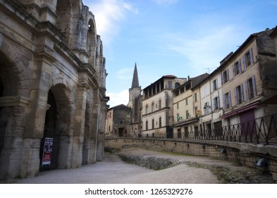 Arles, France - April 29 / 2018 : Arles Amphitheatre at the left side and the houses at the right ride