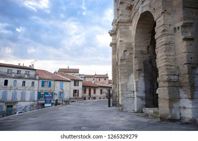 Arles, France - April 29 / 2018 : Arles Amphitheatre at the right side and the houses at the left side