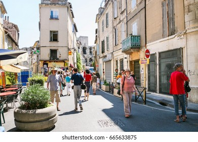 ARLES, FRANCE - JULY 9, 2008: tourists on street and view of Arenes d'Arles (Roman Amphitheater) in Arles city. Arles is ancient city and commune on the south of France in province of Provence.