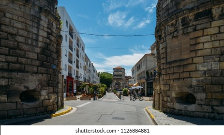 Arles, France - June 16th, 2018: Tourists on street of the historical centre of Arles, an ancient Roman city and commune on the south of France in province of Provence