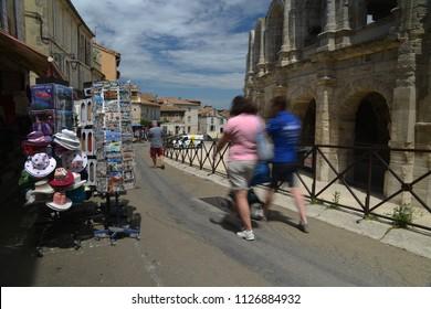 Arles, France - June 16th, 2018: Tourists pass souvenir shops next to the Arenes d'Arles, Roman Amphitheater