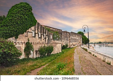 Arles, France: landscape from the riverbank of the Rhone river at sunset with the ancient houses and the bridge