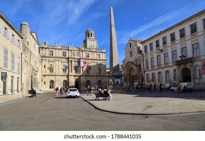 Arles, France - October 3, 2019: People walk on the town square in front of the city hall in Arles, France on October 3, 2019