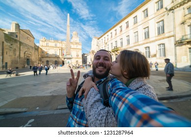 Arles, Provence, France. Happy tourist couple in holiday take selfie photo taveling in Europe trip in the main square of Arles