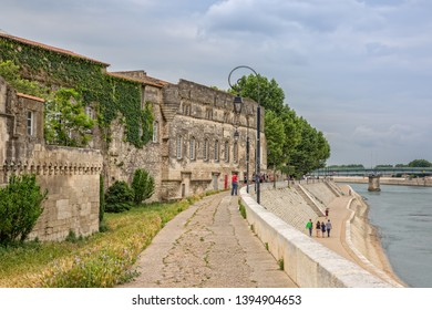 Arles, Provence, Bouches-du-Rhône, France - Jun 03 2017: Peaple walking along the banks of the Rhone. Backview of Musee Reattu overlooking the Rhone and the shore promenade