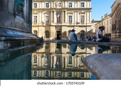 Arles,France-august 14,2016:people near the fountain in the square where the city hall and the obelisk of Arles are located during a sunny day