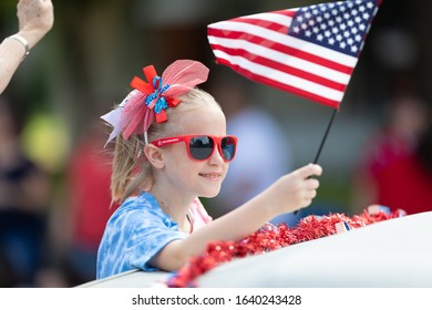 Arlington, Texas, USA - July 4, 2019: Arlington 4th of July Parade, Child on a float waving the American flag during the parade