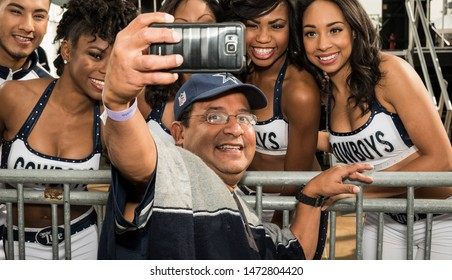 Arlington, Texas / USA - November 1, 2015: Excited Dallas Cowboys Fan Taking a Selfie with the Dallas Cowboys Dancers Outside AT&T Stadium