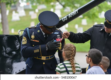 ARLINGTON, USA - MAY 28, 2013 : A veteran soldier explains his medals to the children during a ceremony at Arlington National Cemetery near to Washington DC United States.