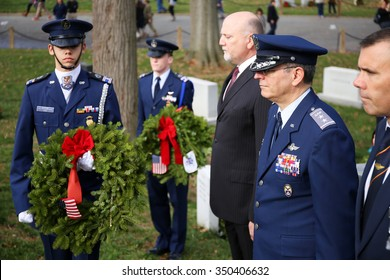 Arlington, VA - December 12 2015: Civil Air Patrol National Commander, Major General Joseph Vazquez, prepares to lay a holiday wreath at a veterans gravesite during Wreaths Across America