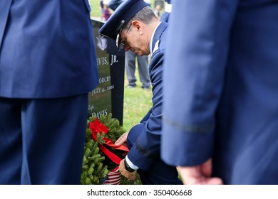 Arlington, VA - December 12 2015: Civil Air Patrol National Commander, Major General Joseph Vazquez, lays a holiday wreath at a veterans gravesite during Wreaths Across America