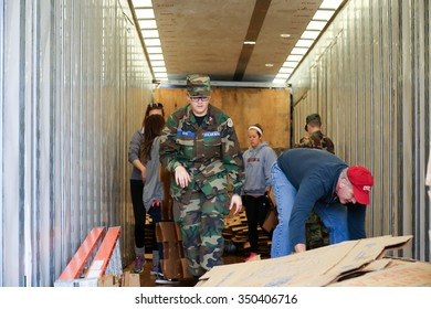 Arlington, VA - December 12 2015: A cadet from the United States Air Force Auxiliary Civil Air Patrol loads empty boxes back into a truck during Wreaths Across America at Arlington National Cemetery
