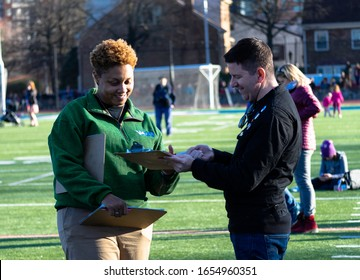 Arlington, VA - February 23, 2020: A campaign worker is gathering petition signatures to get Sen. Mark Warner on the ballot in the upcoming election at an event for Pete Buttigieg in Northern Virginia