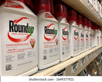 ARLINGTON, VA, USA - FEBRUARY 17, 2020: ROUNDUP product brand logo sign on shelf at home improvement retail store aisle.  ROUNDUP is a glyphosate based herbicide weed and grass killer.