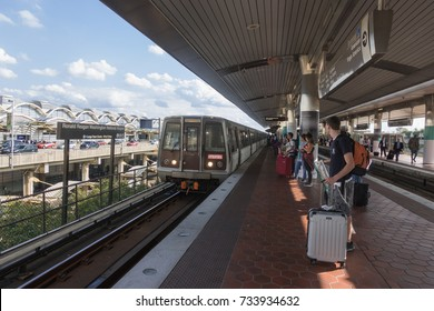 ARLINGTON, VIRGINIA - OCT. 12, 2017: Terminal in background, Reagan National Airport Metro station with travelers on platform. Metro station is connected to terminal by two elevated passageways.