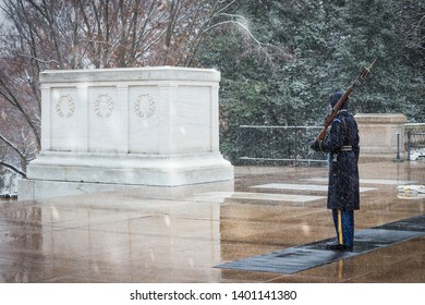 Arlington, Virginia / United States – December 9 2017: A soldier guards the Tomb of the Unknown Soldier during a snowstorm at Arlington National Cemetery.